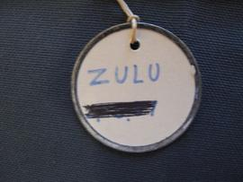 Circular label with metal outline tied to object